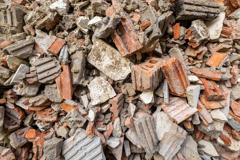 Pilha do tijolo vermelho e do cimento após a construção destruída A parte de parede de tijolo está desintegrando-se do demulido fotografia de stock royalty free