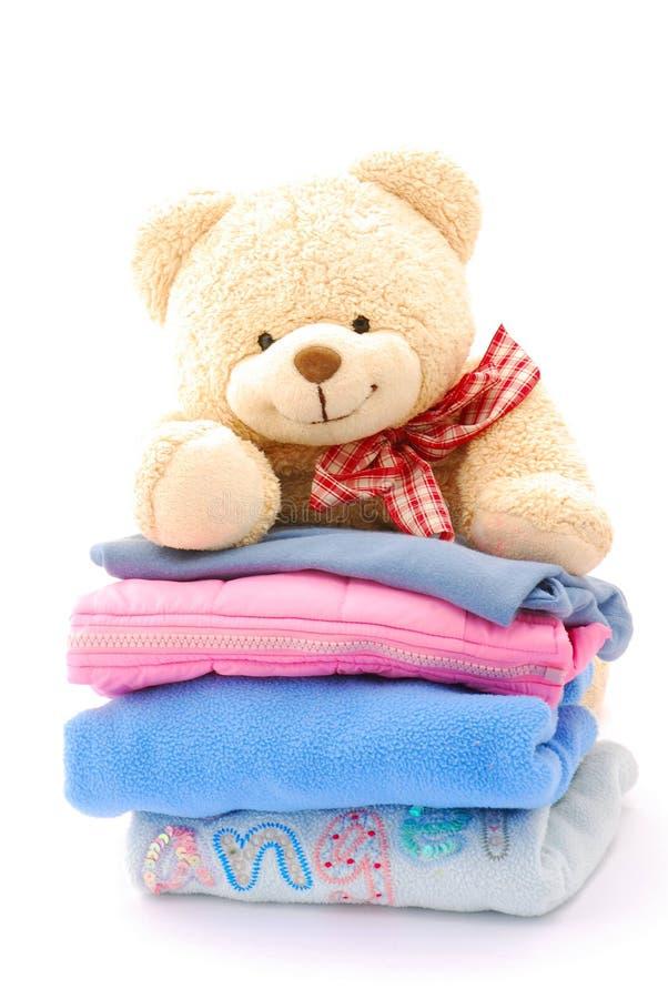 Pilha do urso da peluche de roupa dos miúdos foto de stock