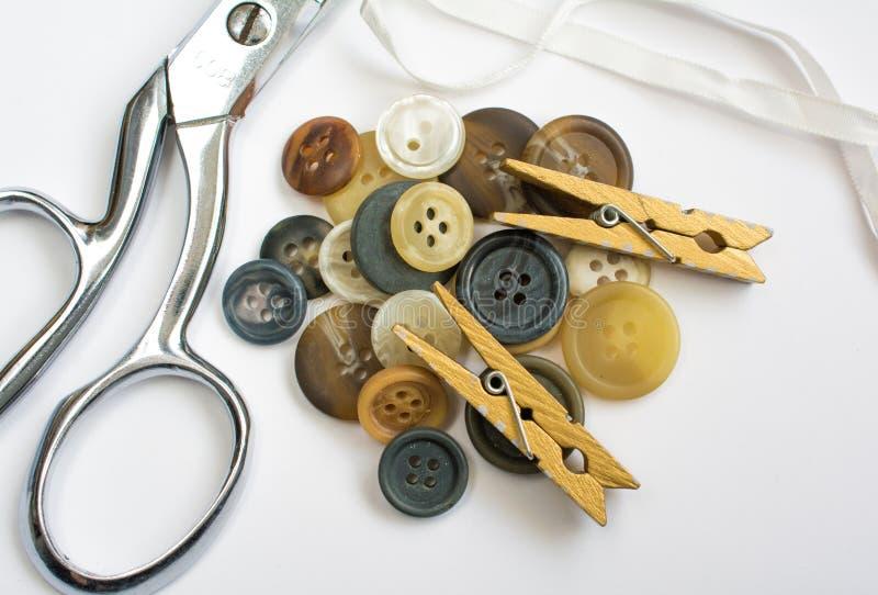 Pilha dos botões com os materiais da costura isolados no branco fotos de stock royalty free