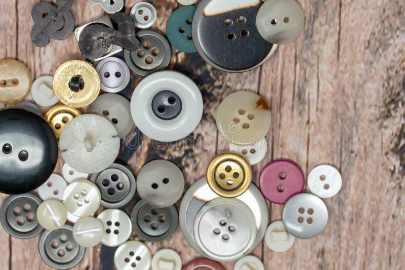 Pilha dos botões costurando brilhantes coloridos aleatórios isolados em um fundo de madeira foto de stock royalty free