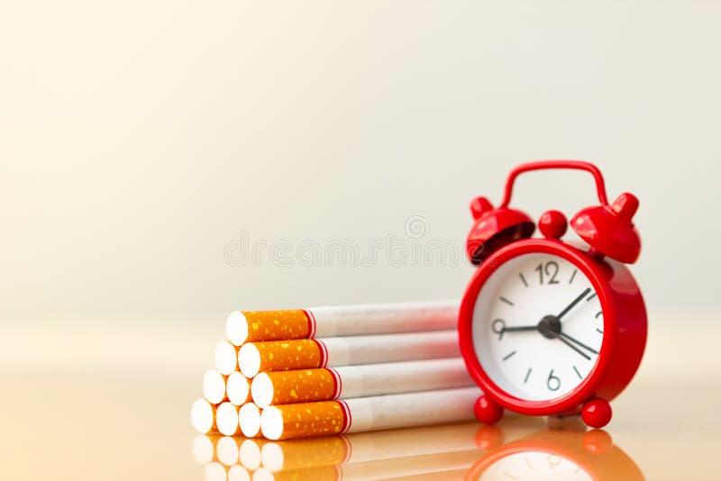 Pilha dos cigarros e despertador vermelho Mundo nenhum dia do tabaco Figura do cigarro e da fam?lia foto de stock royalty free