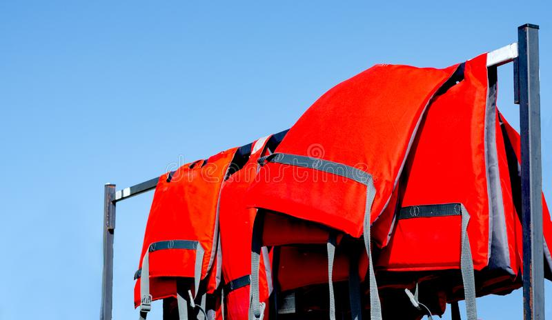 Pilha dos colete salva-vidas vermelhos usados pelos salvadores da água que sentam-se em um ancinho perto da praia durante a tempo foto de stock