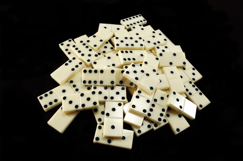 Pilha dos dominós brancos no fundo preto fotografia de stock royalty free