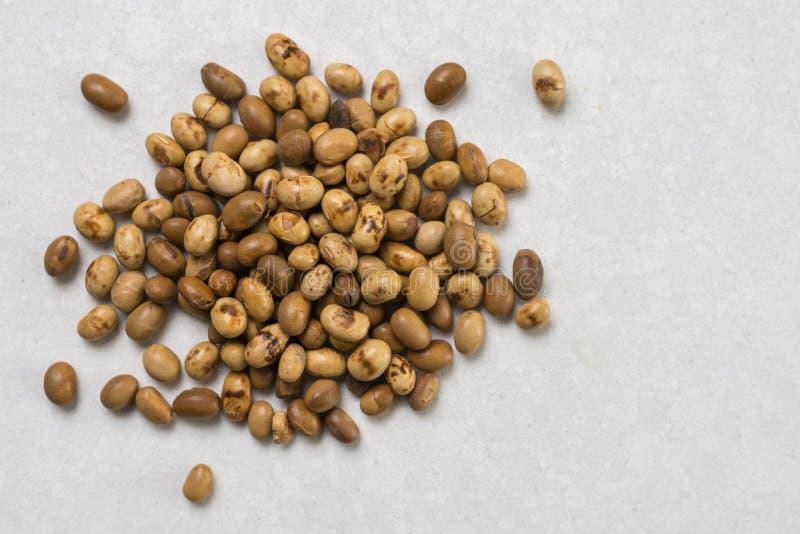 Pilha dos grãos de soja isolados acima do fundo de mármore branco da tabela foto de stock royalty free