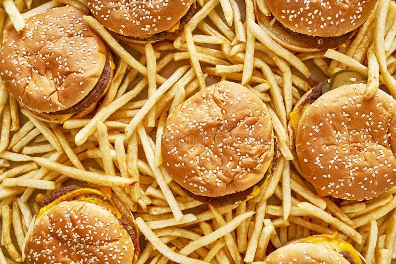 Pilha dos hamburgueres e das fritadas na composição colocada lisa imagem de stock royalty free