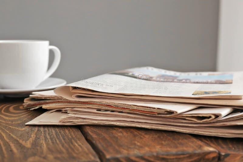 Pilha dos jornais com o copo do chá na tabela de madeira fotografia de stock