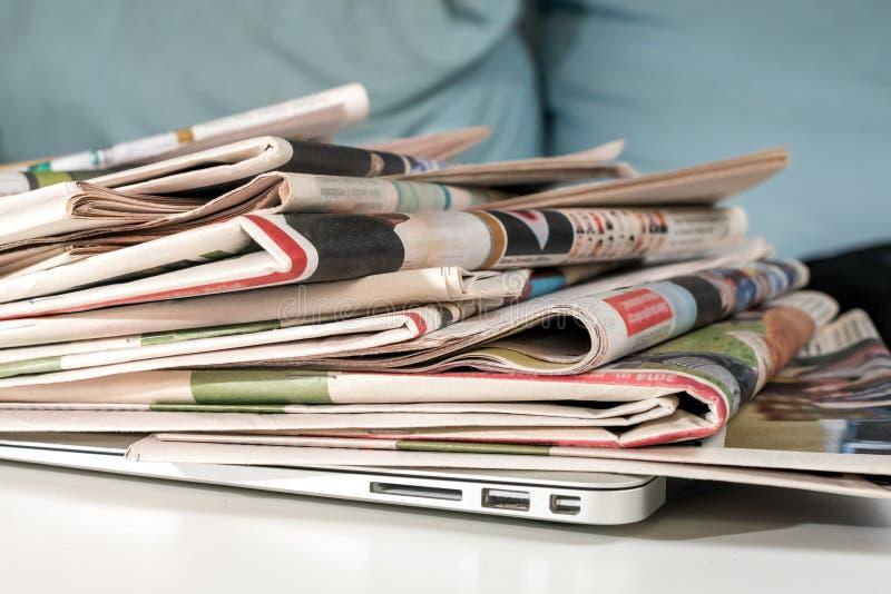 Pilha dos jornais e do portátil fotos de stock royalty free
