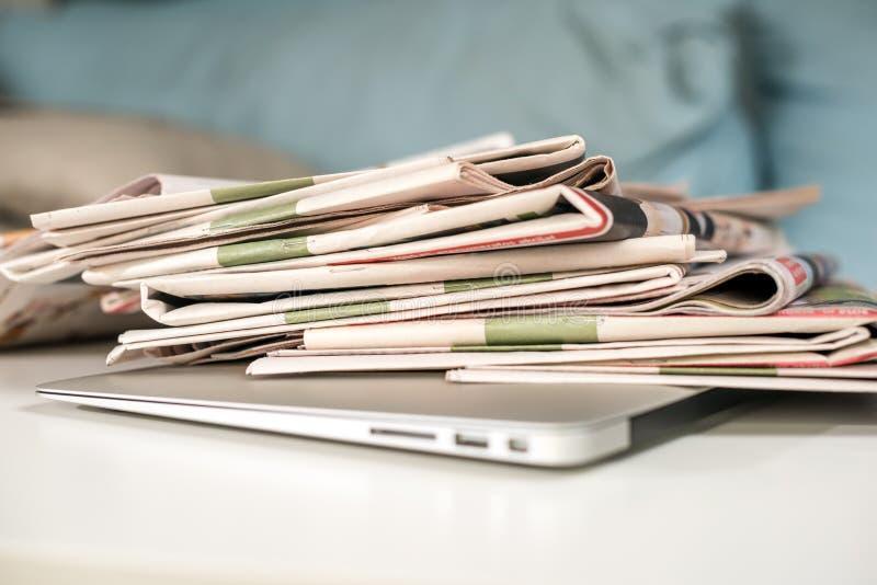 Pilha dos jornais e do portátil imagem de stock