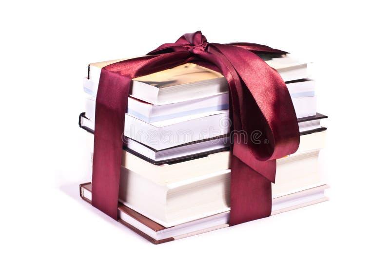 Pilha dos livros de presente amarrados acima com fita vermelha fotos de stock