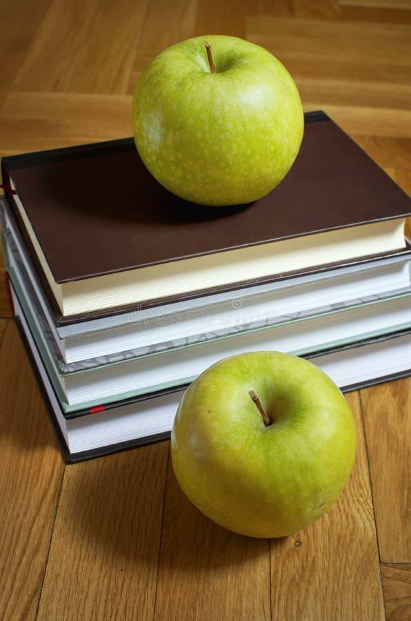 Pilha dos livros e da maçã dois verde no fundo de madeira foto de stock