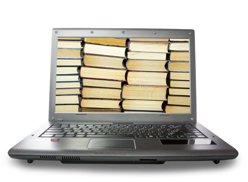 A pilha dos livros em um monitor do portátil, no fundo branco imagem de stock