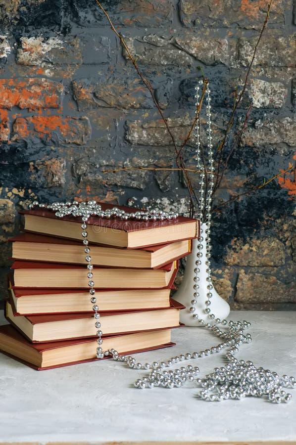 Pilha dos livros velhos, ramos no vaso com festão, backgro do tijolo imagens de stock royalty free