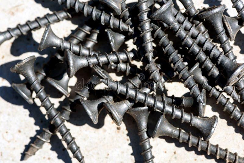 Pilha dos parafusos de madeira pretos no close up macro foto de stock