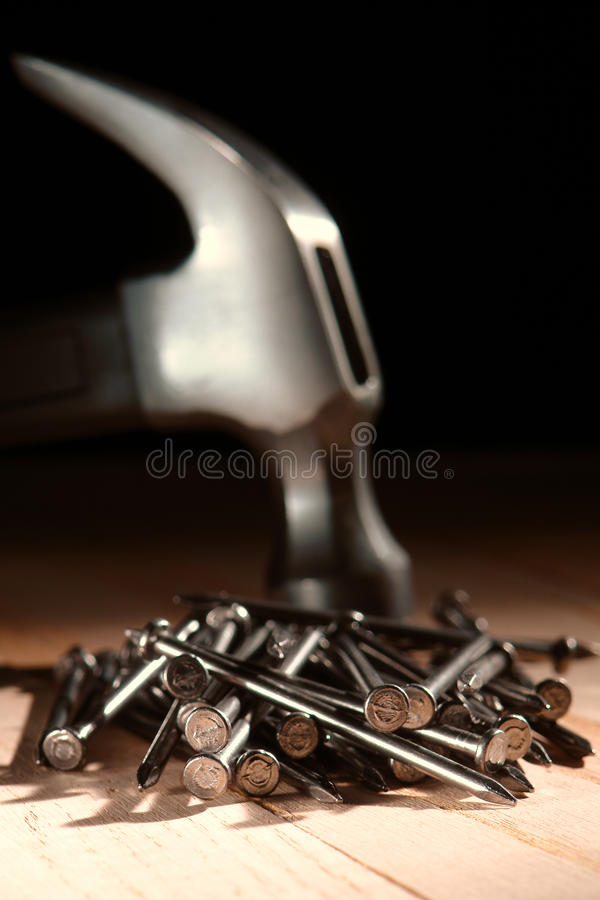 Pilha dos pregos e do martelo de garra no canteiro de obras foto de stock royalty free