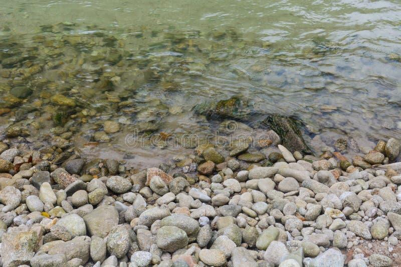 Pilha dos seixos e das pedras ao longo de um rio imagem de stock