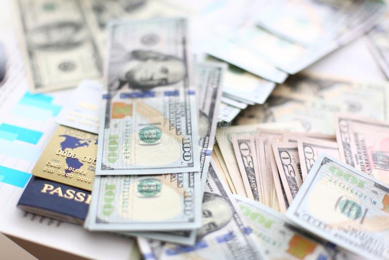 Pilha enorme dos cart?es do passaporte e de banco do dinheiro dos E.U. que encontram-se em gr?ficos financeiros das estat?sticas imagens de stock