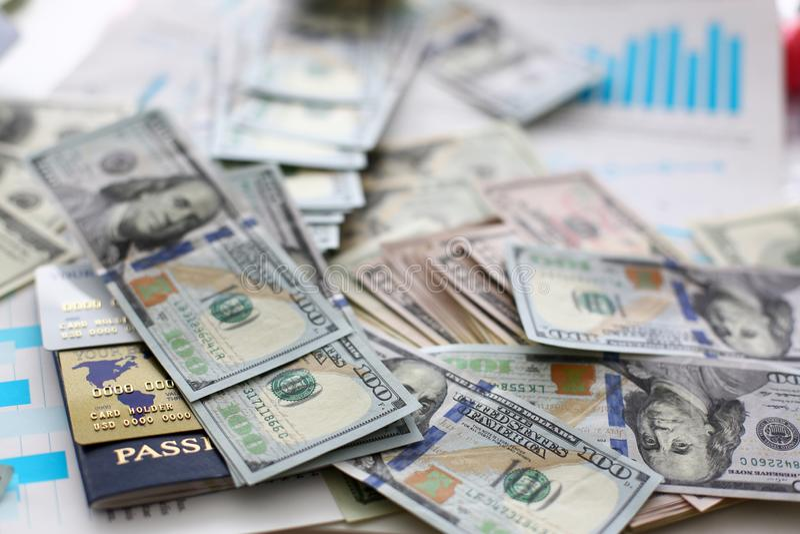 Pilha enorme dos cart?es do passaporte e de banco do dinheiro dos E.U. que encontram-se em gr?ficos financeiros das estat?sticas fotos de stock