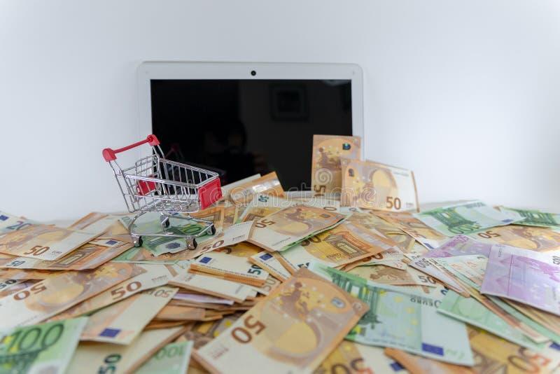 A pilha grande de euro- c?dulas cobre um port?til com o carrinho de compras na parte superior imagem de stock royalty free