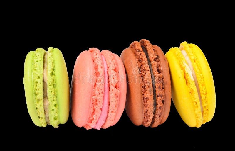 Pilha horizontal de bolinhos de amêndoa pasteis coloridos das cookies isolados no fundo preto fotografia de stock