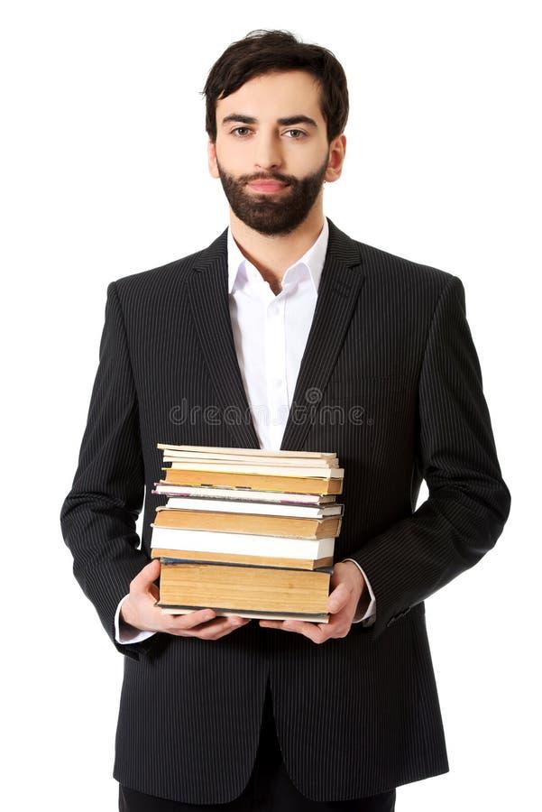 Pilha nova da terra arrendada do homem de negócios de livros fotografia de stock