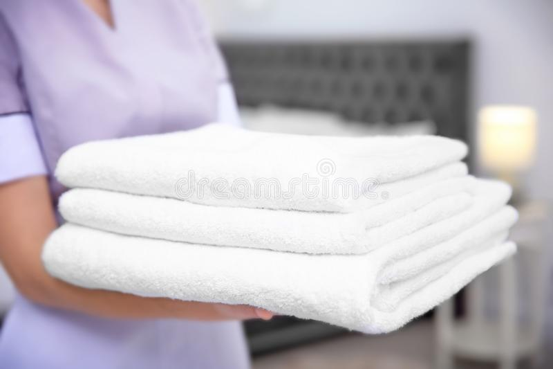Pilha nova da terra arrendada da empregada doméstica de toalhas na sala de hotel imagem de stock royalty free