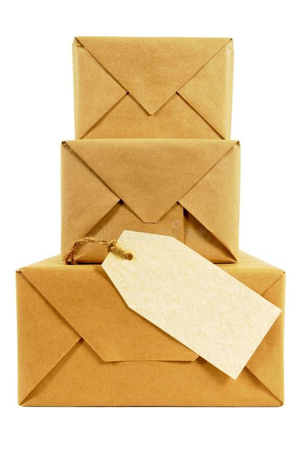 Pilha pequena de pacotes envolvidos, etiqueta de endereço vazia de manila, isolada imagem de stock royalty free