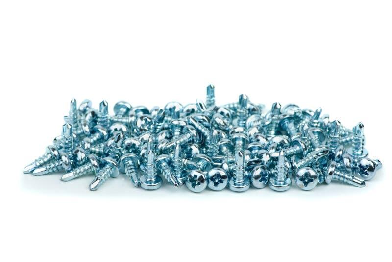 Pilha prata pequena dos parafusos de metal coloridos foto de stock royalty free