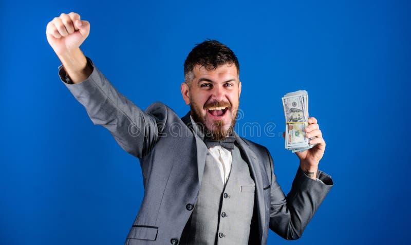 Pilha rica da posse do vencedor feliz do homem do fundo azul das cédulas do dólar Empréstimos de dinheiro fáceis Conceito da lote fotografia de stock