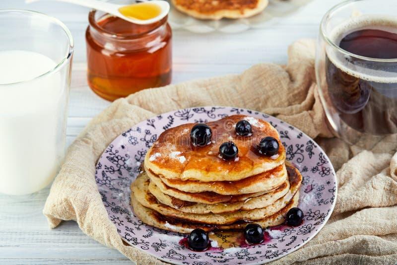 A pilha saboroso do café da manhã A de panquecas com mel transforma um vidro do leite, do café do café e do mel em um branco de m foto de stock royalty free