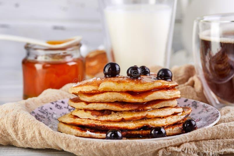 A pilha saboroso do café da manhã A de panquecas com mel transforma um vidro do leite, do café do café e do mel em um branco de m fotos de stock royalty free