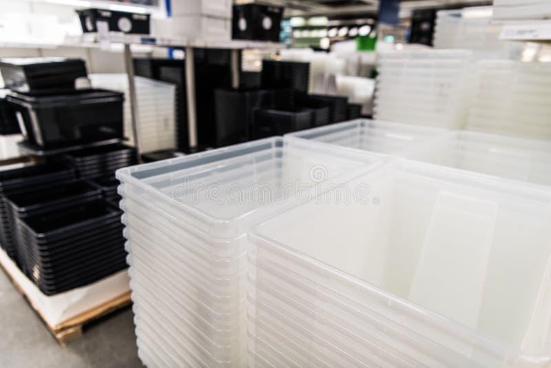 Pilha transparente e preta dos recipientes plásticos em uma loja foto de stock