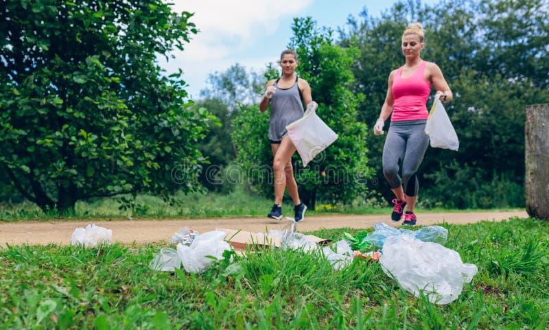 Pilha Waste e duas meninas que fazem plogging foto de stock royalty free