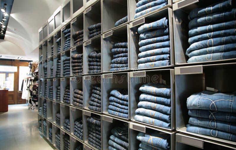 Pilhas com as calças de brim na loja imagem de stock