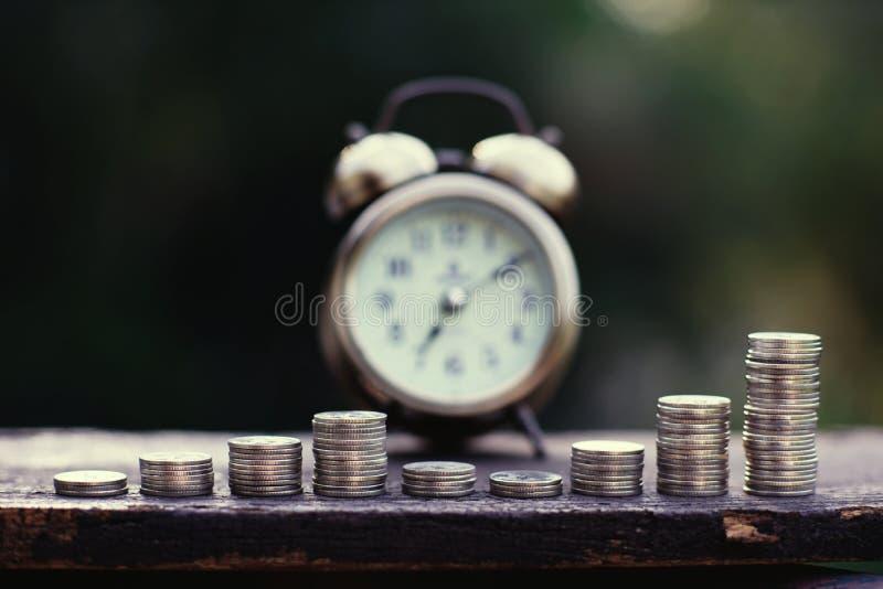 Pilhas da moeda arranjadas na etapa do ciclo de negócio, para cima e para baixo, e despertador do vintage na tabela de madeira co imagem de stock