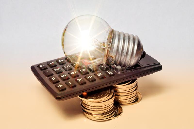 Pilhas da moeda, calculadora, e ampola fotografia de stock royalty free