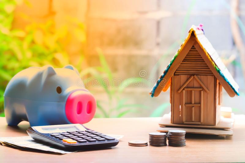 Pilhas da moeda, modelo da casa, calculadora e mealheiro, planos das economias para abrigar fotografia de stock