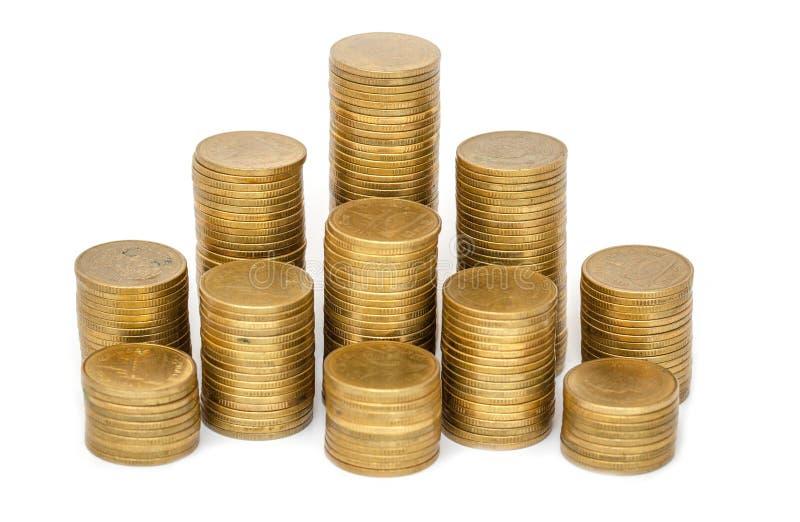 Pilhas das moedas de ouro isoladas no fundo branco Economia, negócio crescente da pilha da moeda Conceito do dinheiro do investim foto de stock