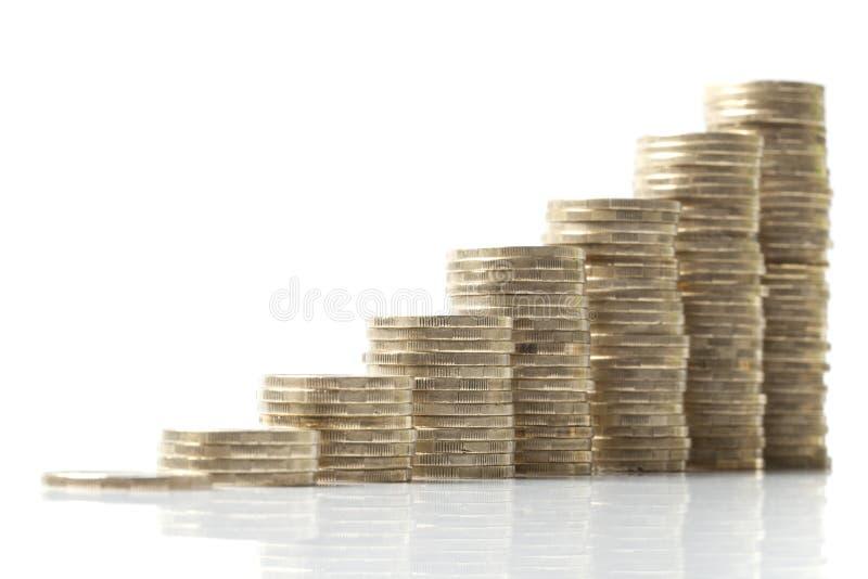 Pilhas de ascensão das moedas no branco fotos de stock