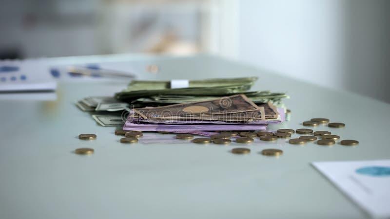 Pilhas de cédulas e de moedas na tabela, divisa estrageira, salário do salário, dinheiro fotos de stock