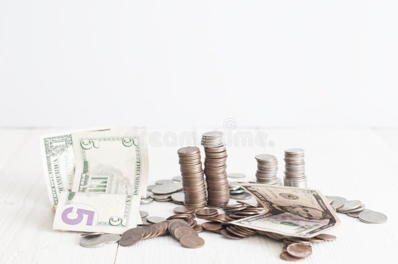 Pilhas de centavos americanos e de 5, 1 dólar de cédulas fotografia de stock