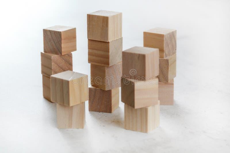 Pilhas de cubos de madeira do brinquedo que criam torres pequenas na placa branca fotos de stock