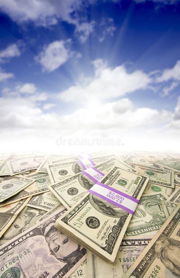 Pilhas de dinheiro, de Sunburst e de céu azul imagem de stock