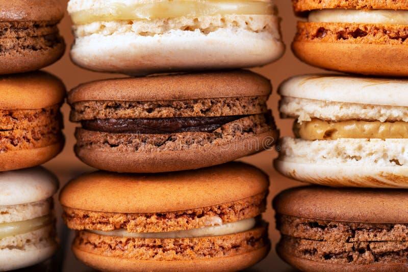 Pilhas de macarons ou de bolinhos de amêndoa franceses marrons e brancos, de chocolate, de café, do caramelo salgado e da baunilh imagem de stock