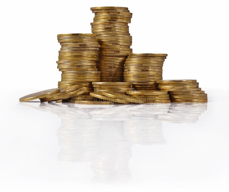 Pilhas de moedas de ouro em um branco foto de stock