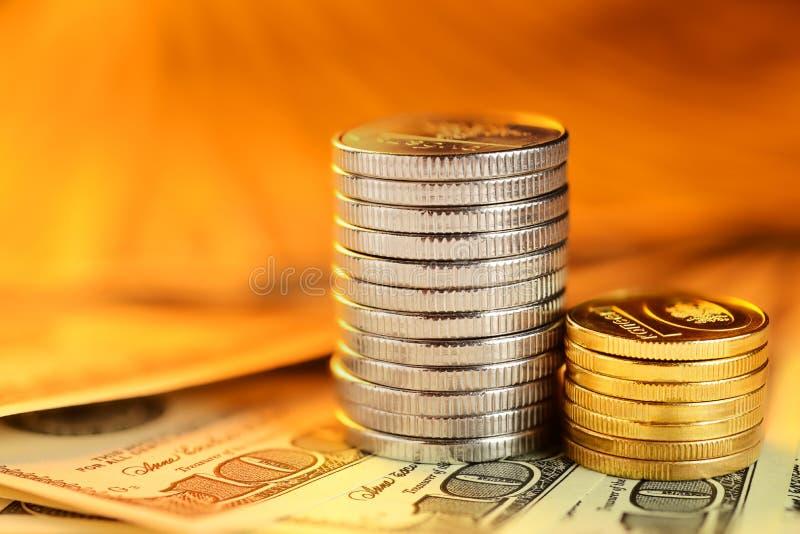 Pilhas de moedas e de notas de dólar fotografia de stock