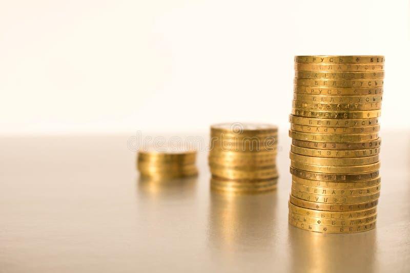 Pilhas de moedas em um fundo claro Conceito do negócio e crescimento do capital fotos de stock
