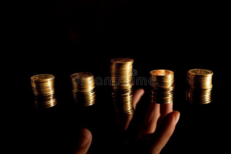 Pilhas de moedas no alcance escuro do fundo e da mão foto de stock royalty free