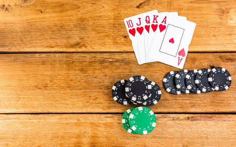 Pilhas de poker chips e recarga real sobre fundo de madeira, poker chips espalhados, grandes cegos, traficantes, conceito de pôqu imagens de stock