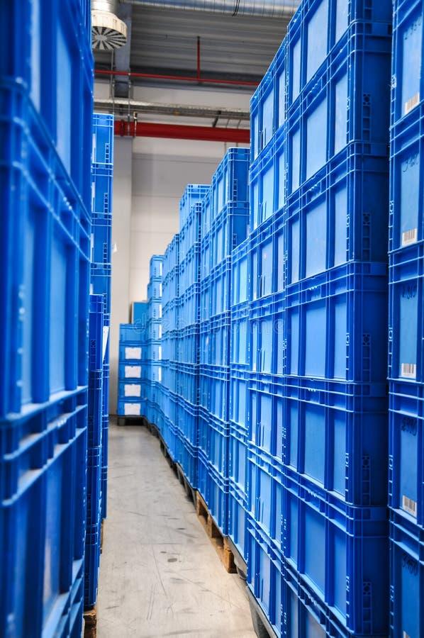 Pilhas de recipientes plásticos azuis em um armazém em Alemanha foto de stock royalty free