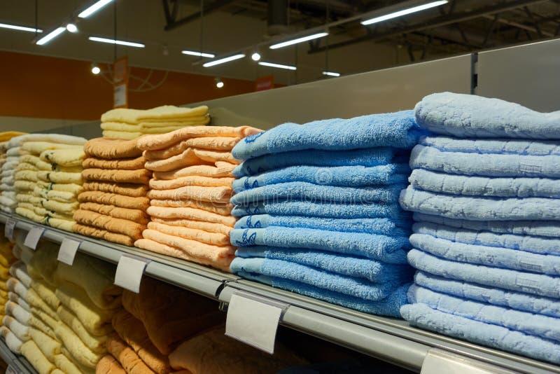 Pilhas de toalhas dobradas na prateleira na loja foto de stock